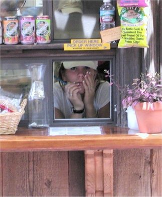 A young girl inside the window of a snack service shack.