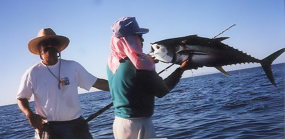 two men in boat one with a pole and one holding up a huge tuna